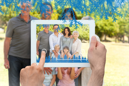 Hands holding tablet pc against family standing in the park photo