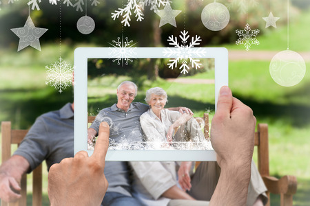 Hands holding tablet pc against senior couple sitting on a bench photo