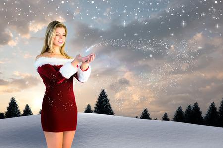 pere noel sexy: Jolie fille se tenant la main dans Santa tenue contre la neige qui tombe sur la for�t de sapin