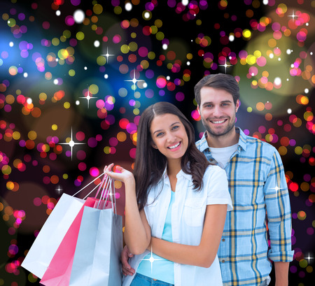 Happy couple with shopping bags against colourful glowing dots on black photo