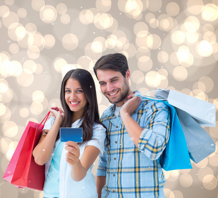 Couple with shopping bags and credit card against light glowing dots design pattern photo