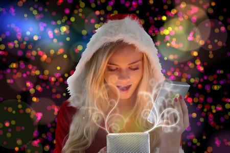 pere noel sexy: Sexy Santa Girl cadeau d'ouverture contre les points brillants color�s sur fond noir Banque d'images