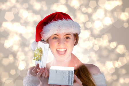 Sexy girl in santa costume opening a gift against light glowing dots design pattern photo
