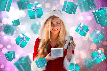 pere noel sexy: Sexy santa girl ouverture cadeau contre des points brillants de lumi�re sur pourpre