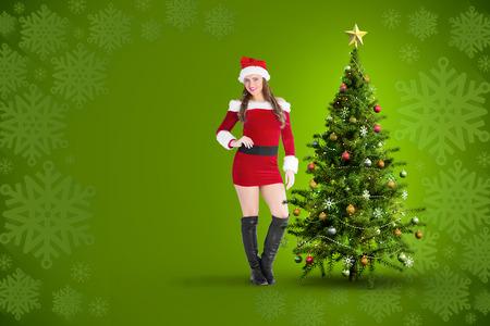pere noel sexy: Sexy Santa Girl souriant � la cam�ra contre flocon vert motif d'encadrement de conception Banque d'images