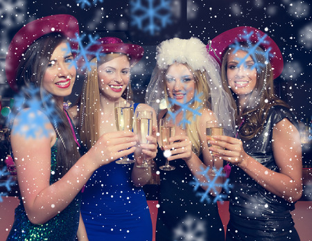 Attractive friends clinking champagne glasses at hen night against snowflakes photo