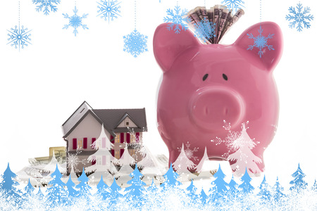 Snowflakes and fir trees against close up of a pink piggy bank with dollars beside miniature house model photo