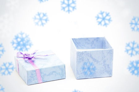 baby open present: Snowflakes against open blue gift box with purple ribbon Stock Photo