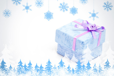 Snowflakes and fir trees against blue gift box with purple ribbon photo