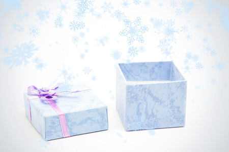 baby open present: Snow falling against open blue gift box with purple ribbon