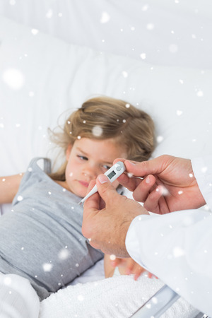 Doctor holding thermometer with ill girl in hospital against snow falling photo