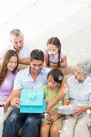 gifting: Cumplea�os regalos en familia presente al hombre contra la nieve que cae Foto de archivo