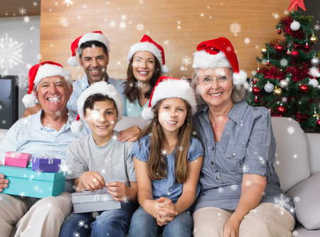 Extended family in Christmas hats with gift boxes in living room against snow falling photo
