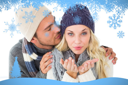 Attractive couple in winter fashion  against snow flake frame in blue photo