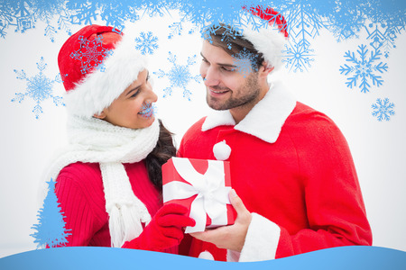 Attractive festive couple holding a gift against snow flake frame in blue photo