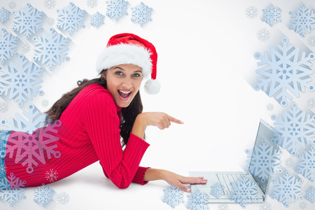 Beautiful festive woman pointing to laptop against snowflake frame photo