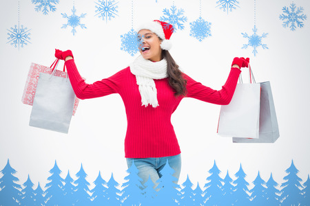 Beautiful festive woman holding shopping bags against snowflakes and fir trees in blue photo