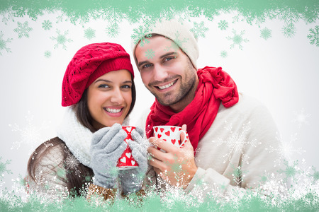 Attractive young couple in warm clothes holding mugs against snow flake frame in green photo
