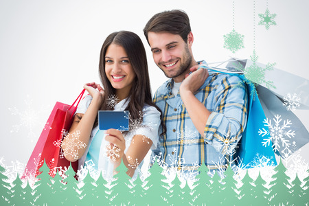 Attractive young couple with shopping bags and credit card against snowflakes and fir trees in green photo