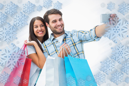 Attractive young couple with shopping bags taking a selfie against snowflake frame photo