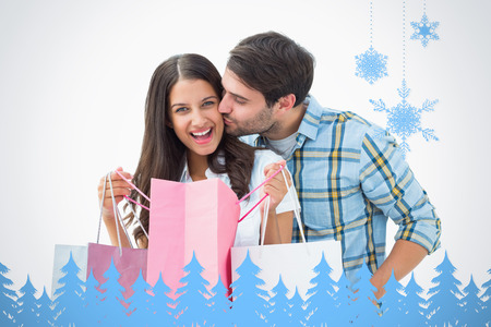 Attractive young couple with shopping bags against snowflakes and fir trees in blue photo