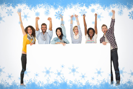 Smiling group of young friends showing large poster and cheering against snow flake frame in blue photo