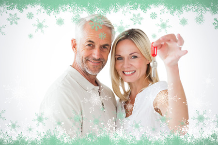 Happy couple showing their new house key against snow flake frame in green photo