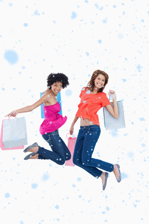 Young teenagers energetically jumping after going shopping against snow falling