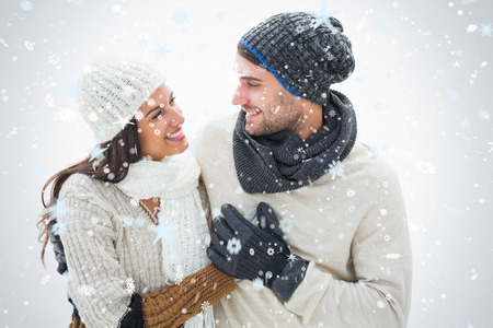 attractive man: Attractive young couple in warm clothes against snow falling Stock Photo