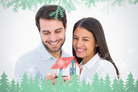 Attractive young couple holding a model house against frost and fir trees in green photo