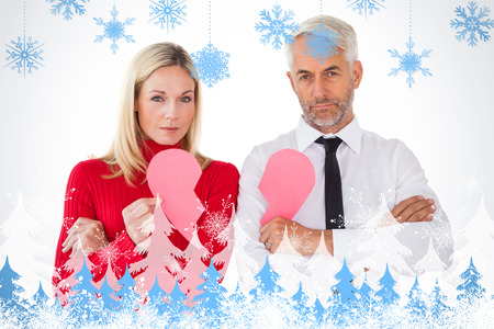 Couple not talking holding two halves of broken heart against snowflakes and fir trees photo
