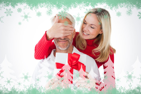 Smiling woman covering partners eyes and holding gift against green snowflake design photo