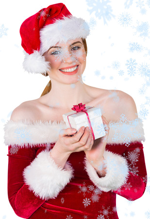 Pretty girl in santa costume holding gift box against snow falling photo