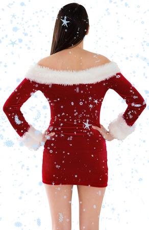 pere noel sexy: Santa girl debout avec les mains sur les hanches contre des chutes de neige