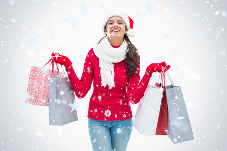Beautiful festive woman holding shopping bags against snow falling photo