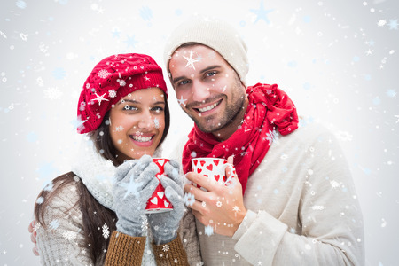 mixed race couple: Attractive young couple in warm clothes holding mugs against snow falling