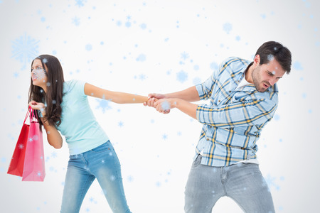 Attractive young man pulling his shopaholic girlfriend against snow falling photo