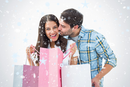Attractive young couple with shopping bags against snow falling photo