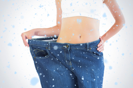body concern: Close up of confident slender blonde wearing too big trousers against snow falling Stock Photo