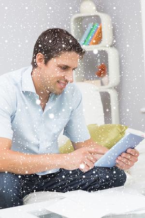 figuring: Smiling man with bills using digital tablet in the living room against snow falling Stock Photo
