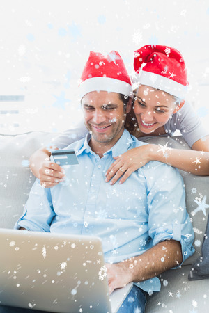 Cute couple in santa hats shopping online with laptop against snow falling photo