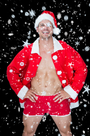 Smiling muscular man posing in sexy santa outfit against snow falling photo