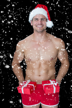 Smiling muscular man posing in sexy santa outfit offering gifts against snow falling photo