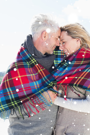 hair wrapped up: Happy couple wrapped up in blanket standing on the beach against snow falling