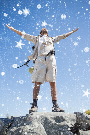 Handsome hiker standing at the summit against snow falling photo