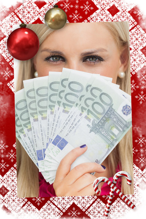 Green eyed woman holding 100 euros banknotes against christmas themed page photo