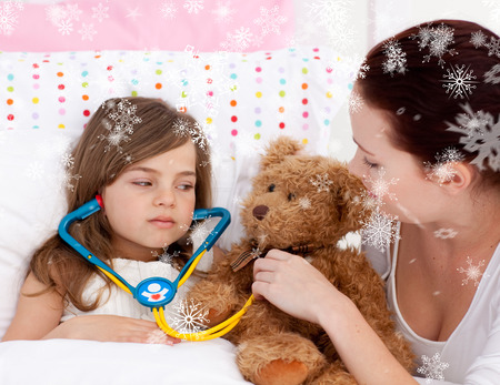 Composite image of Sick daughter playing with a stethoscope with her mother with snowflakes photo