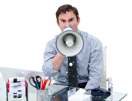 Composite image of Furious businessman yelling through a megaphone sitting at his desk with snow falling photo