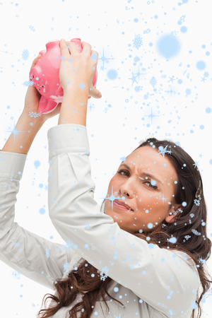 Portrait of a brunette woman holding an empty piggy bank against snow falling photo