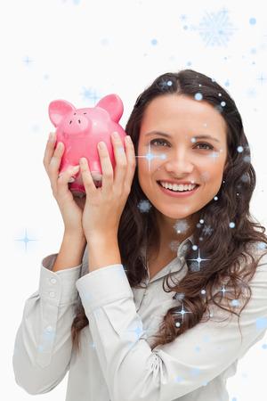 Portrait of a brunette shaking a piggy bank against snow falling photo